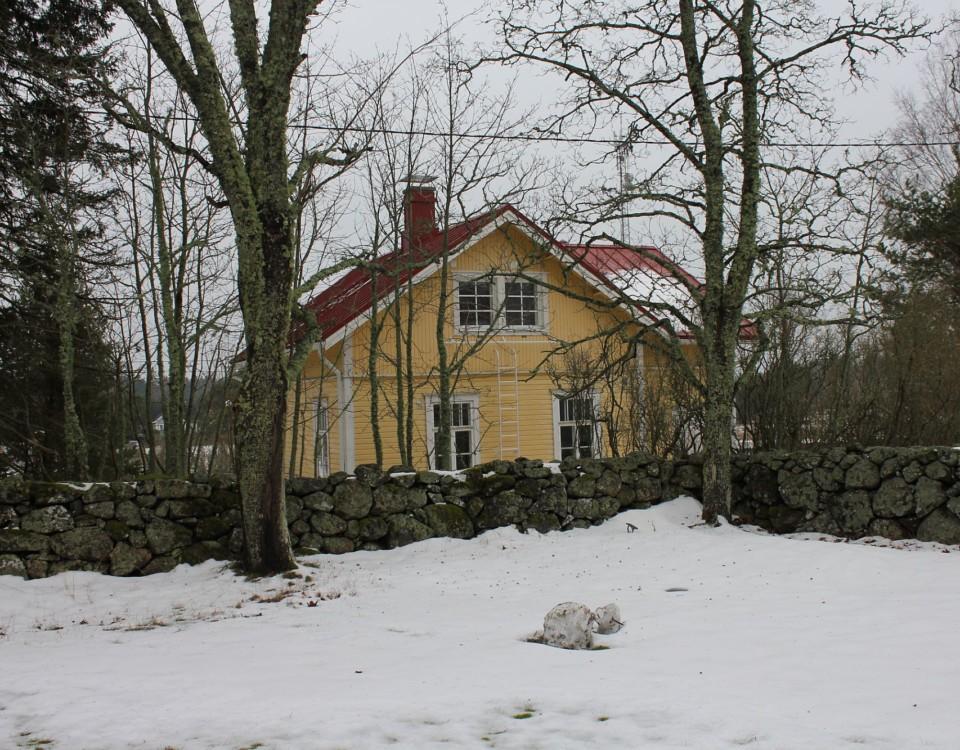 ett gult hus i ett snöigt landskap
