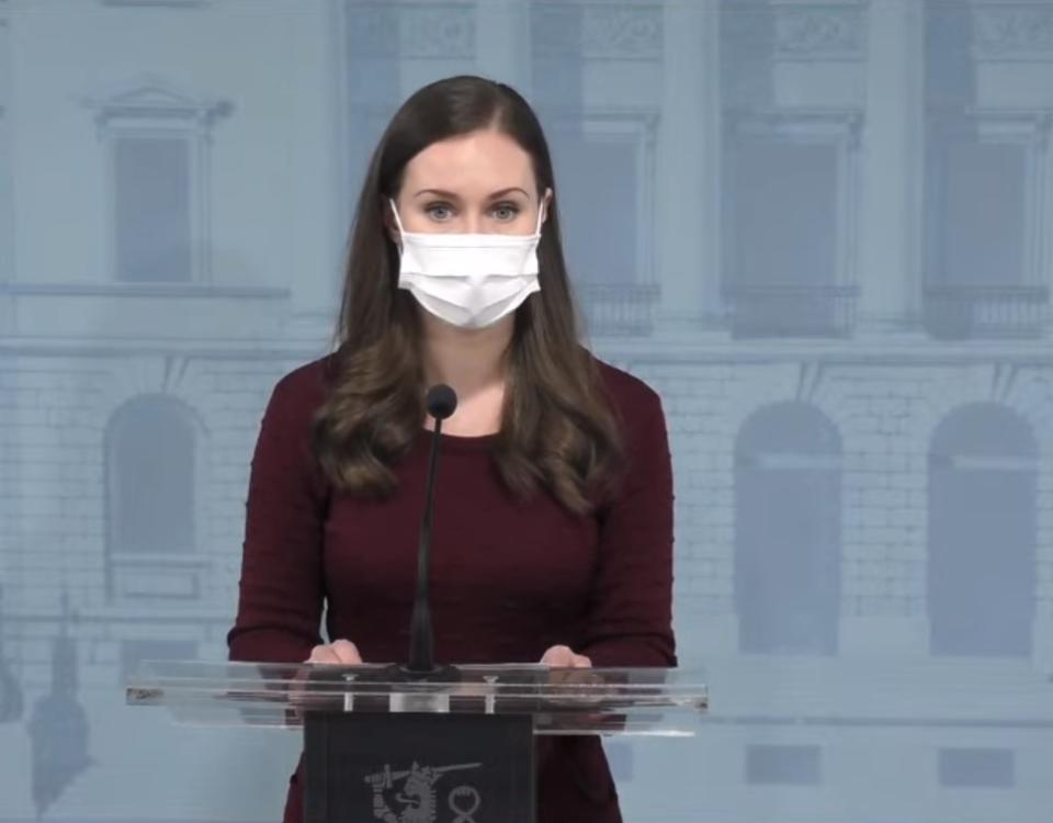 Sanna Marin iklädd munskydd talar mikrofon på presskonferens.