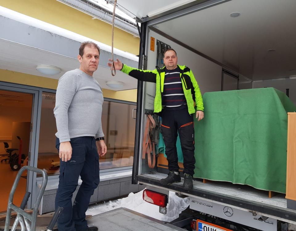två män på rampen till en välfylld flyttbil