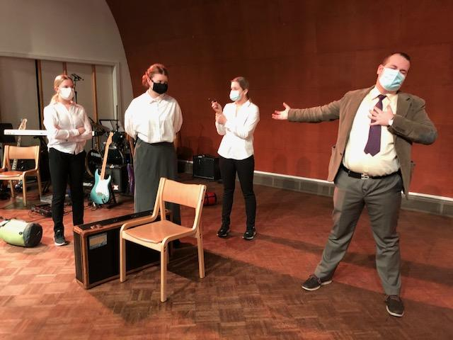 elever på en scen, alla har på sig munskydd