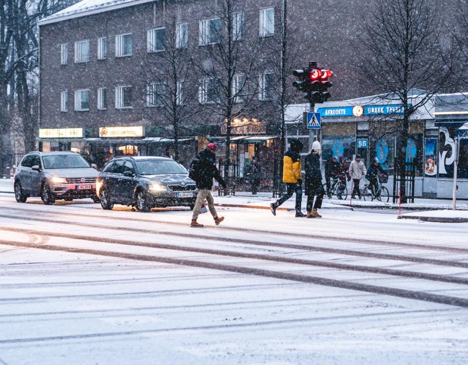 personer korsar väg i snöstorm
