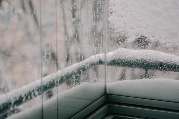 Snö samlat på utsidan av balkongglas