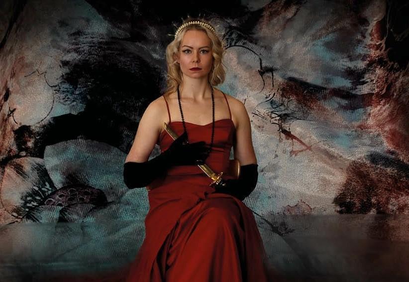 Kvinna iklädd röd balklänning sitter på en stol och tittar allvarligt in i kameran. Bilden är planschen till pjäsen Till Fedra.