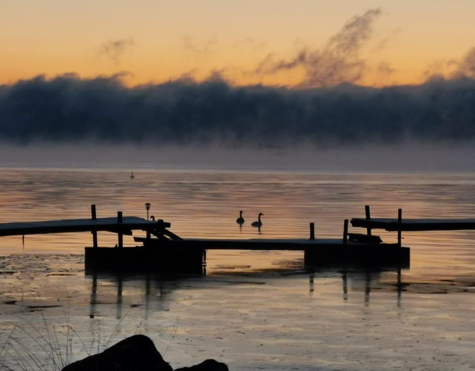 soluppgång över vik med brygga. Tunn is, längre ut sjörök.