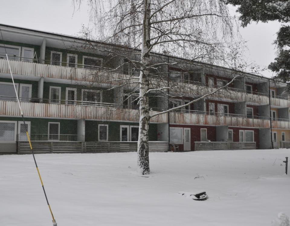 Bostadshus i tre våningar med sliten fasad.