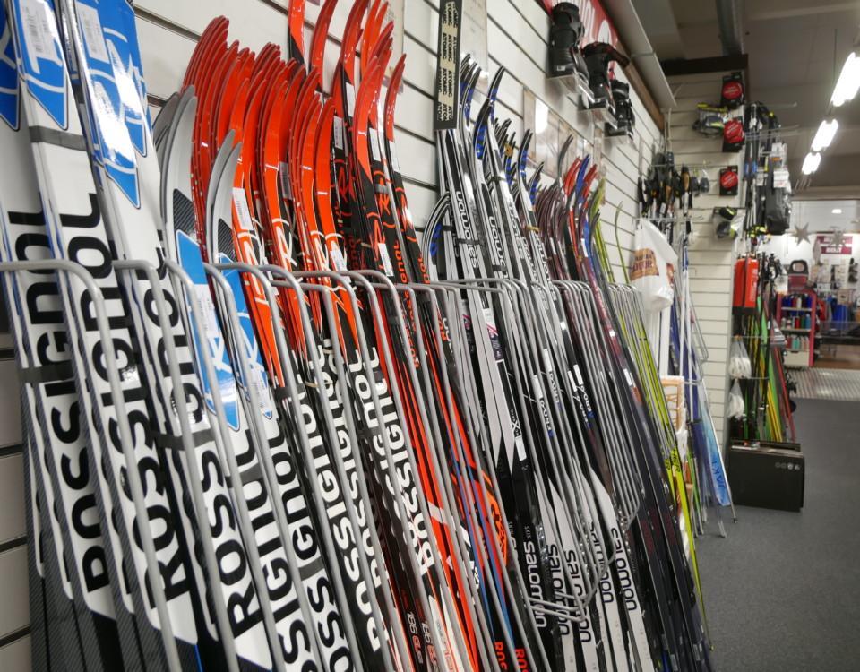 Skidor radade längs vägg i sportaffär.