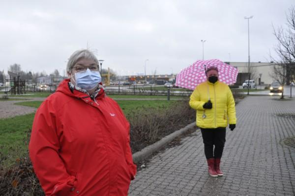 Två damer på en trottoar vid en park