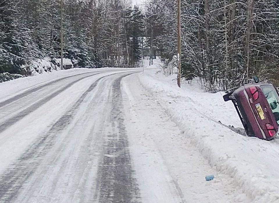 bil i diket vid landsbygdsväg med mycket snö