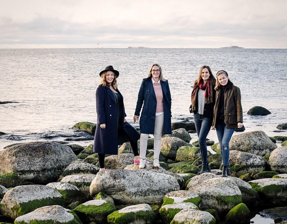 Fyra kvinnor står på strandstenar