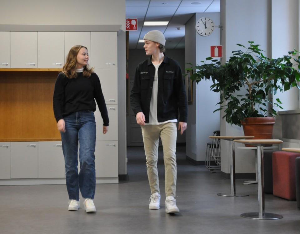 ung kivnna och ung man går leende i en skol-aula