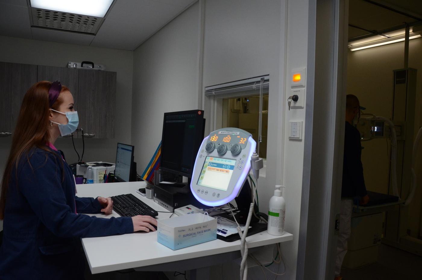 kvinna står vid ett skribord där en apparat med många siffor lyser