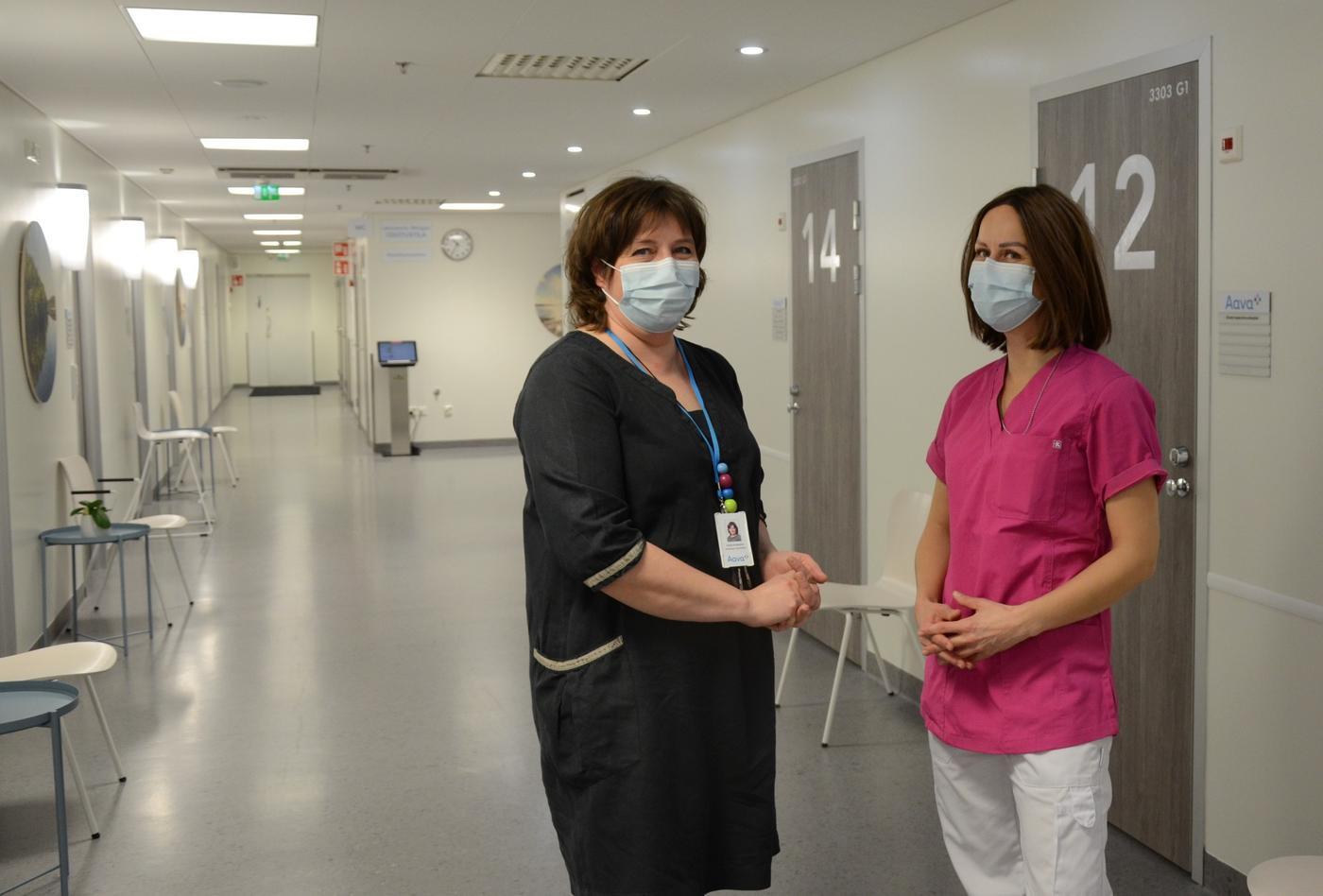 två kvinnor står i en korridor, de bär munskydd och den ena är sjukskötarklädd