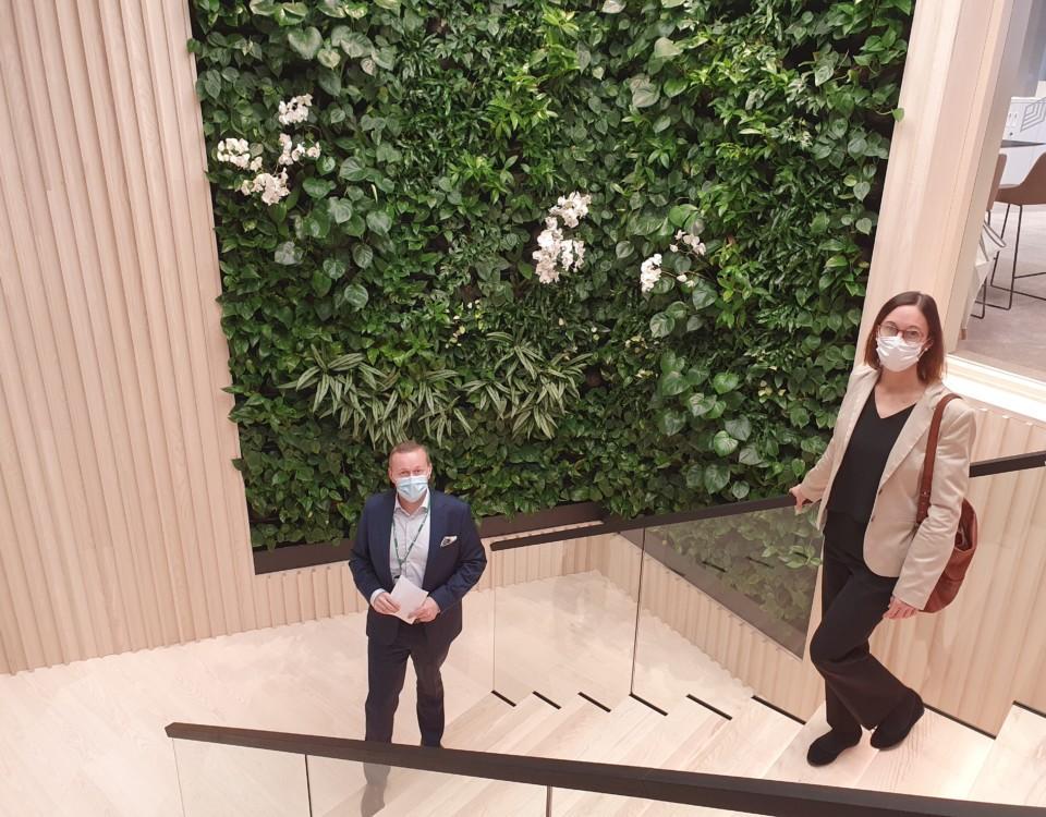 trappa med grön fondvägg, två personer står i trappan