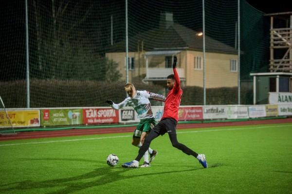 två fotbollsspelare i kamp om bollen