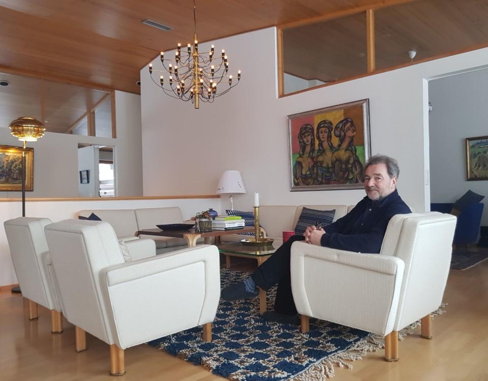 en man i ett vardagsrum i en vit soffa