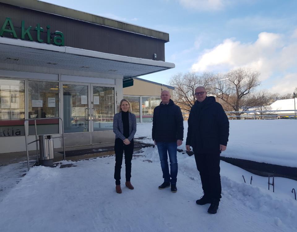en kvinna och två män utanför en banklokal på vintern