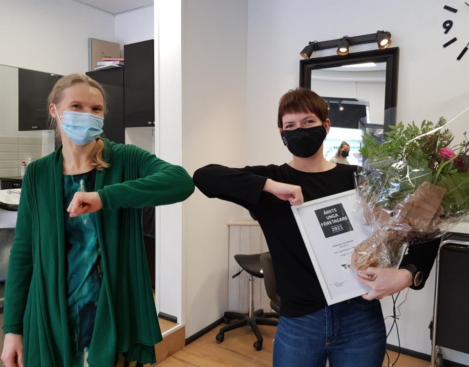 Två kvinnor med munskydd armbågs hälsar. Den högra har en blombukett
