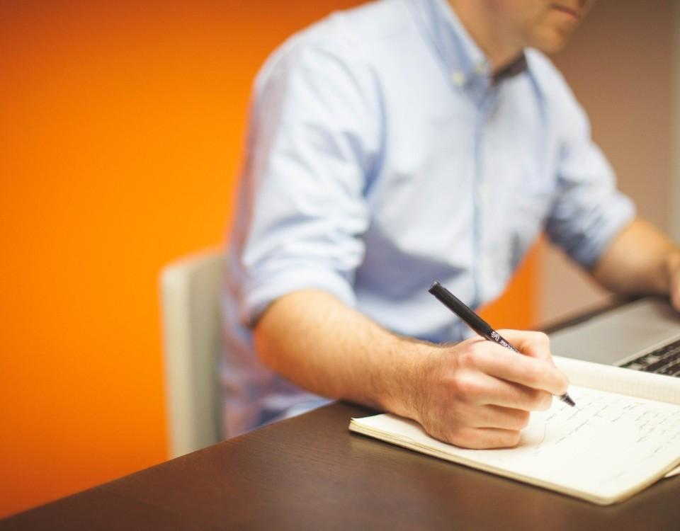 Man som skriver något på ett papper.