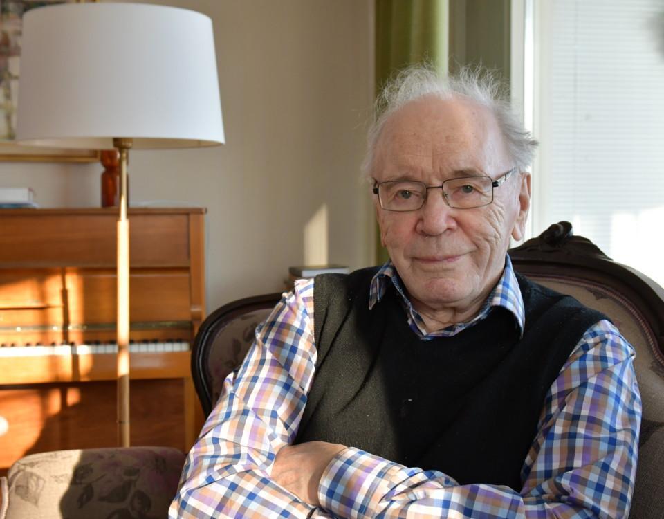 äldre man sitter i fåtölj