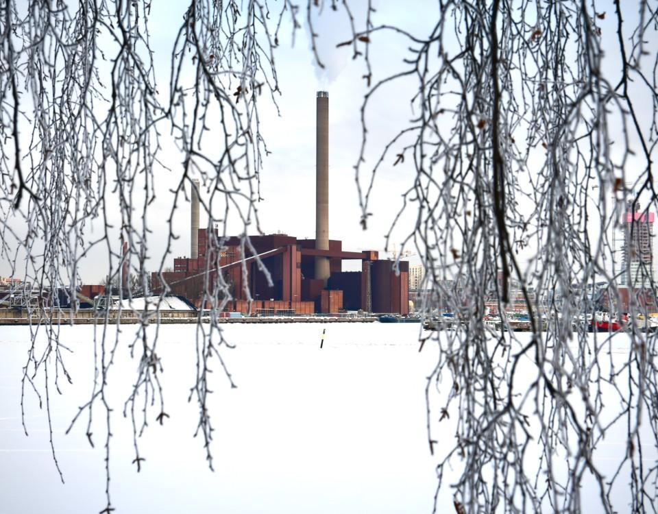 Ett kraftverk fotat på avstånd. Omgivningen är vintrig med snö på marken.