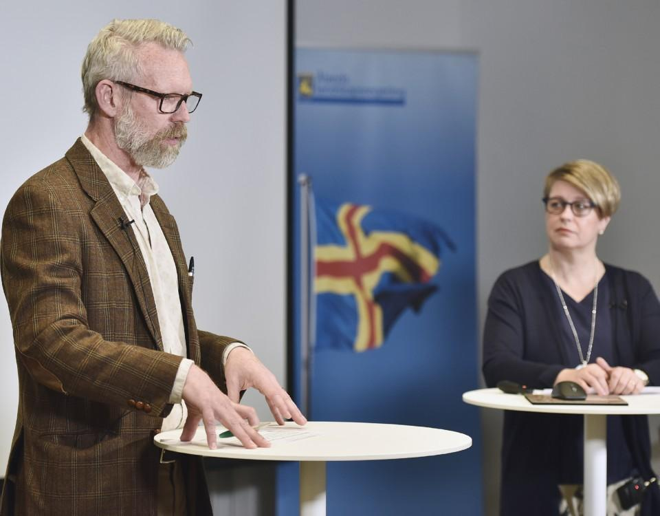 En man iklädd brun kostym står framför ett bord och talar. I bakgrunden syns en kvinna, samt en plansch med Ålands flagga.