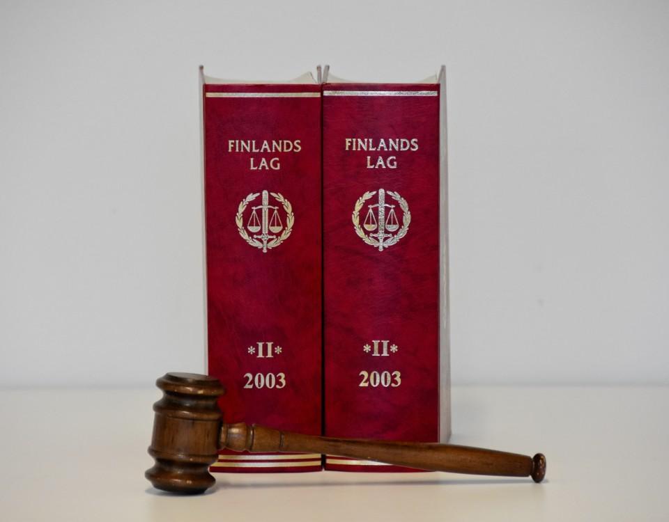 Två röda lagböcker och en domarklubba.
