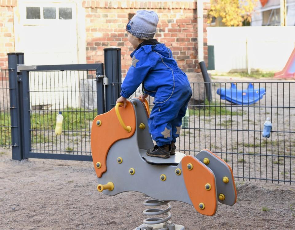 Ett barn på en gunghäst i en lekpark.