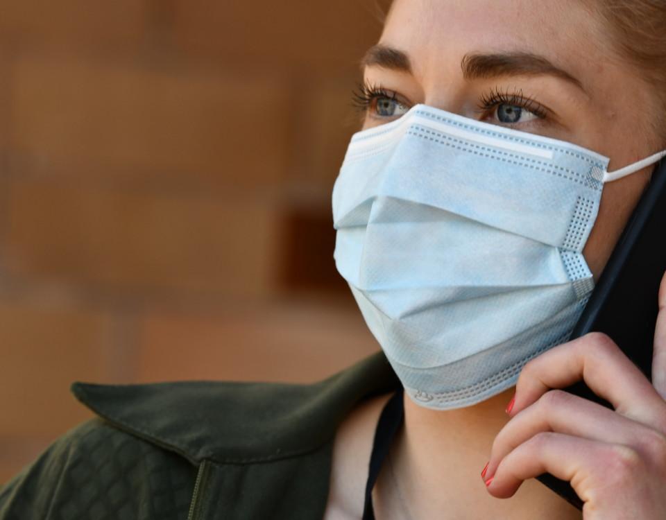 Kvinna med munskydd talar i telefon.