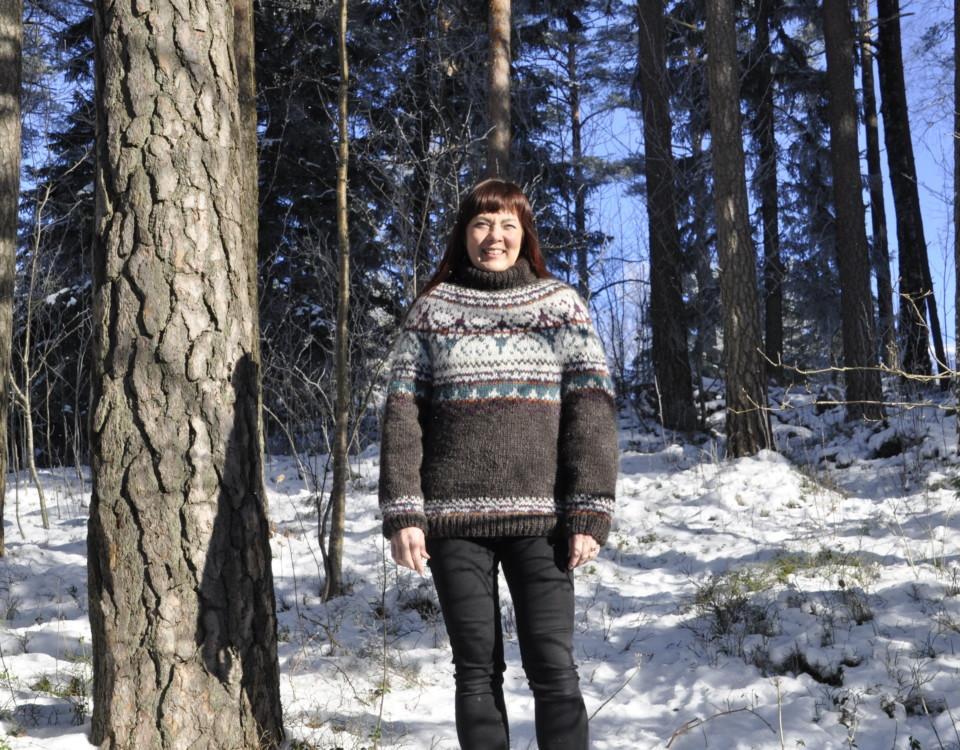 dam i ylletröja bland tjocka trädstammar i en snöig skog