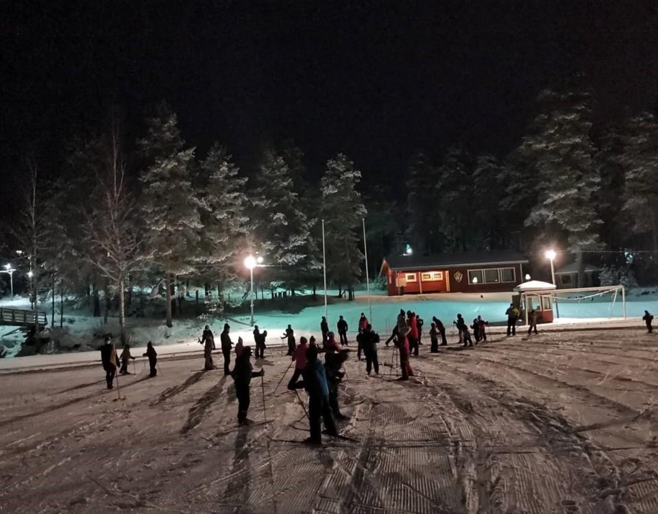 Många barn syns bakifrån vid en mindre skidanläggning
