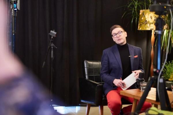Man sitter på stol i tv-studio