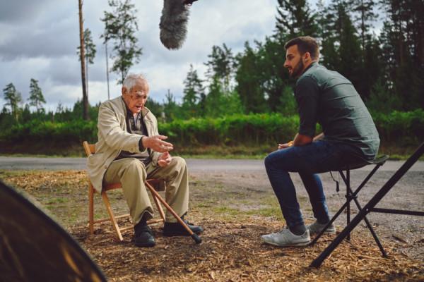 En ung man intervjuar en krigsveteran. De sitter på stolar utomhus, bilden är tagen en sommardag.
