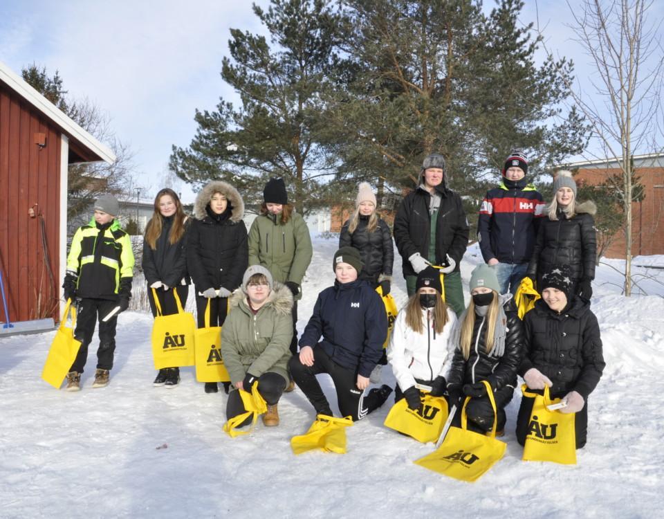 En grupp ungdomar utomhus med gula ÅU-kassar