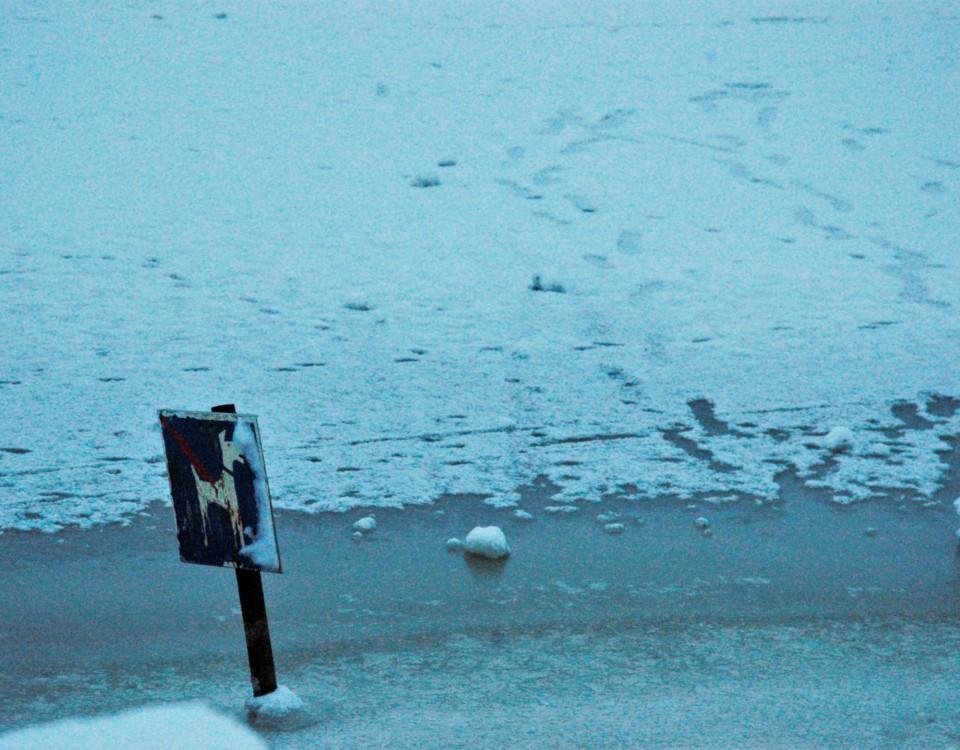 varningsskylt för hundar fastfrusen i is