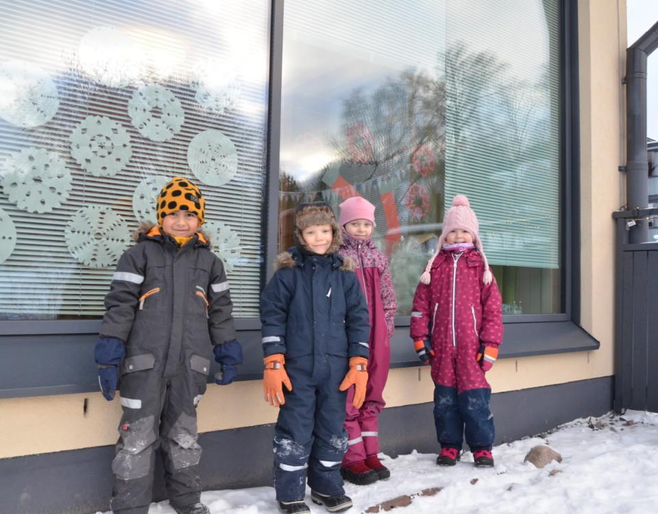 fyra förskolebarn i vinterkläder