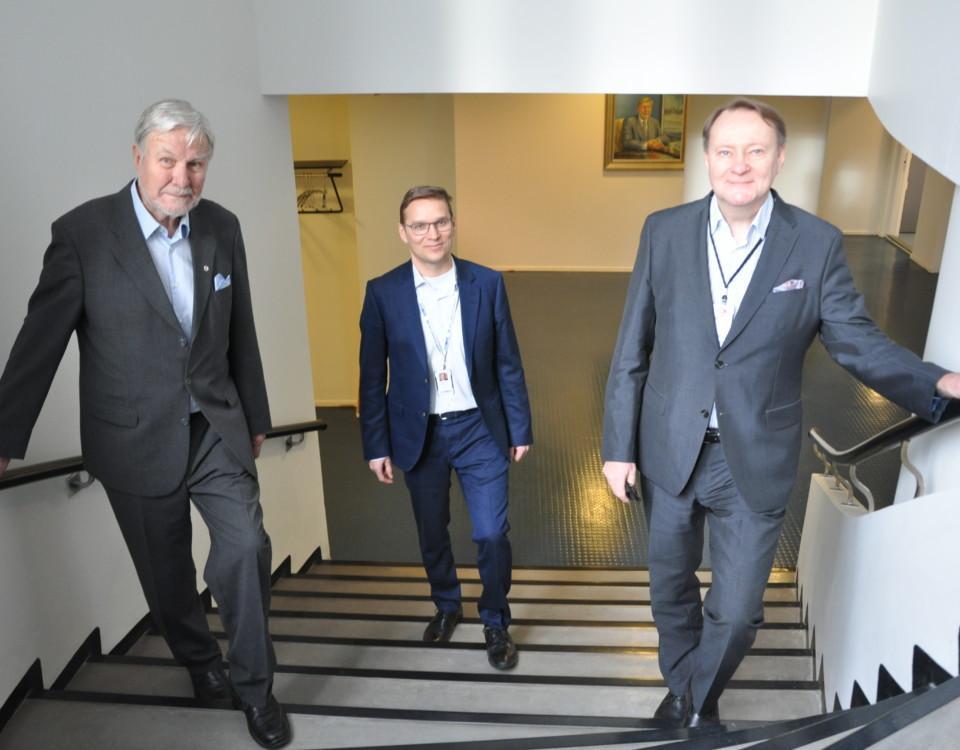 Tre män står i en trappa i ett kontorshus