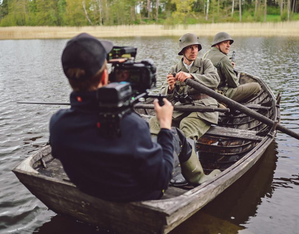 Man med kamera filmar skådespelarsoldater i roddbåt