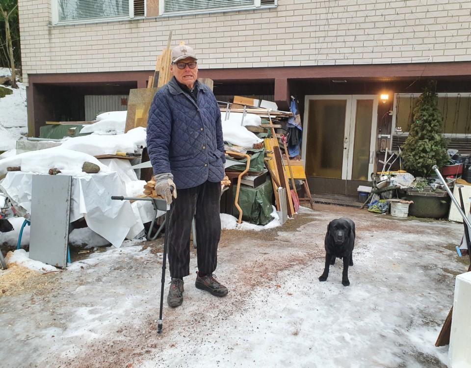 Äldre man med käpp tillsammans med en svart labradortik.