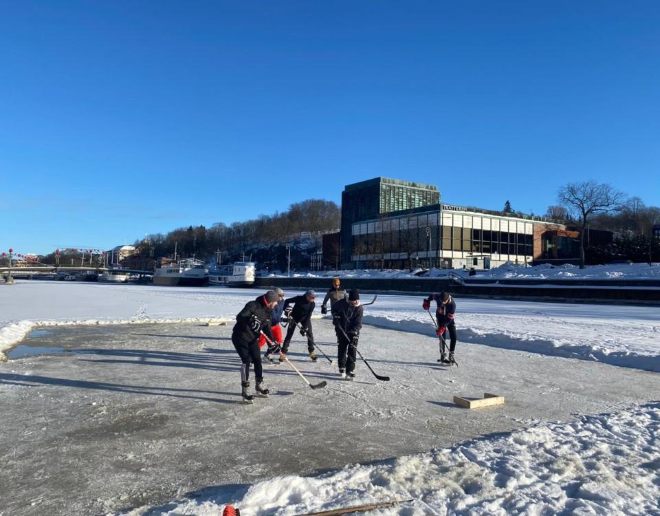 Några ishockeyspelare spelar på ån i strålande solsken. De har skottat upp en liten plätt där de spelar.