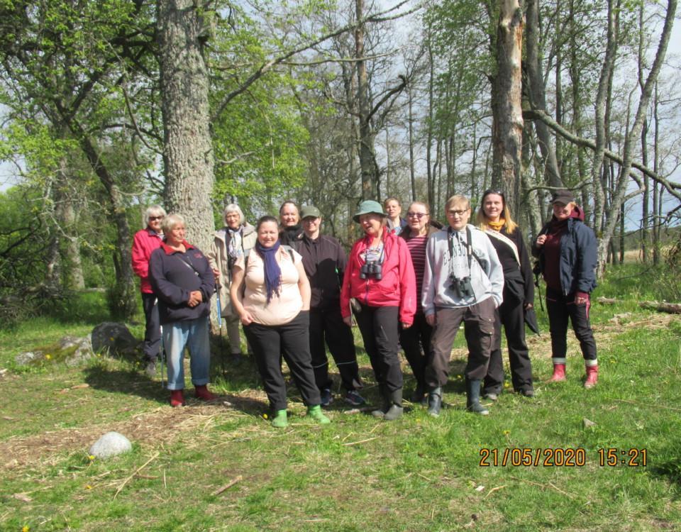 En grupp med människor ler mot kameran. Bilden är tagen utomhus på våren, solen skiner och omgivningen är grön.