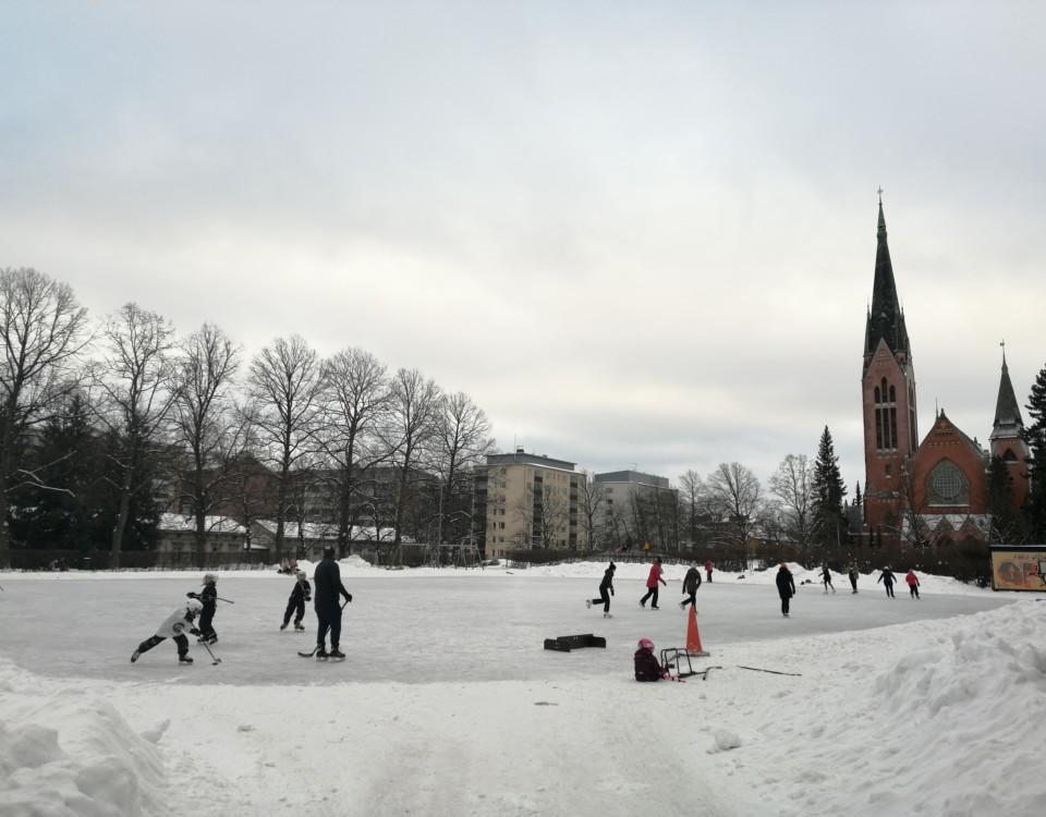 En skridskobana fylld av folk. I bakgrunden syns Mikaelskyrkan.