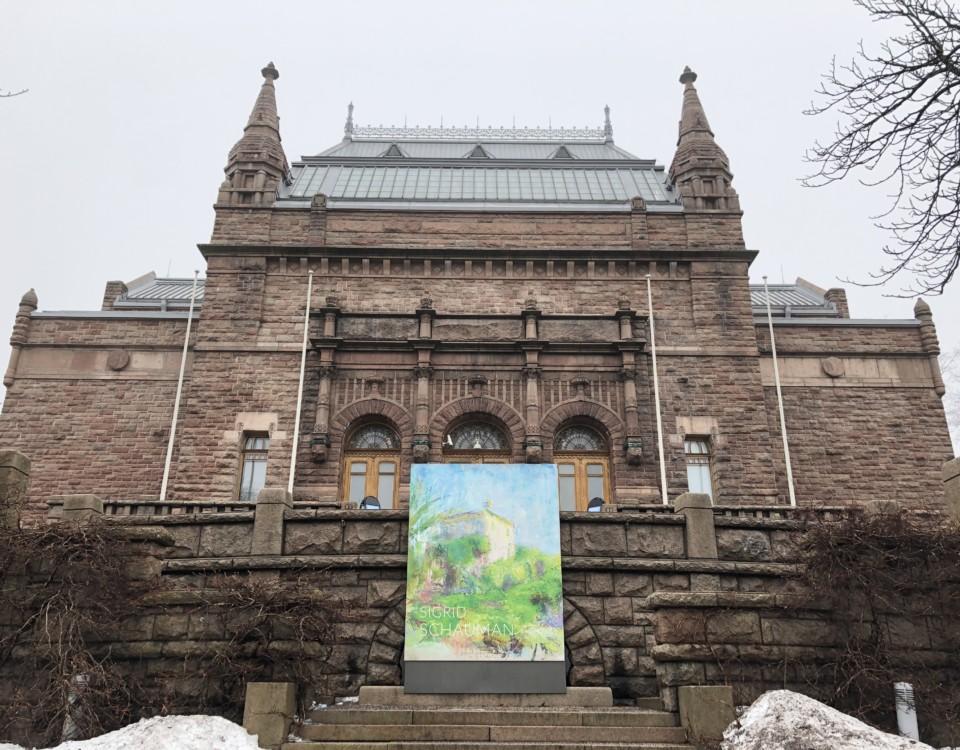 Stor brun byggnad med ett konstverk framför.