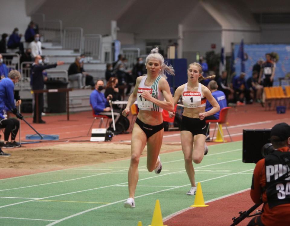 Två kvinnor löper på friidrottsbana inomhus.