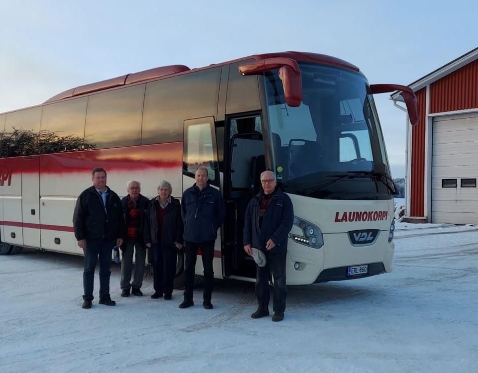 En turistbuss- Fem personer står bredvid den.