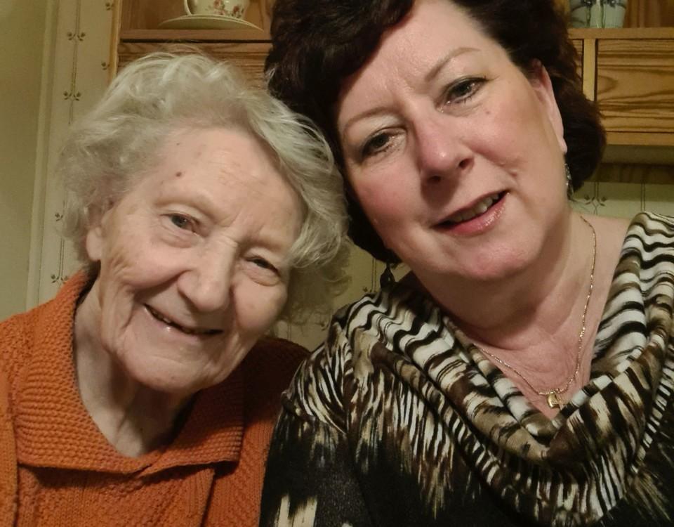 En äldre och en yngre dam med huvudena tätt ihop