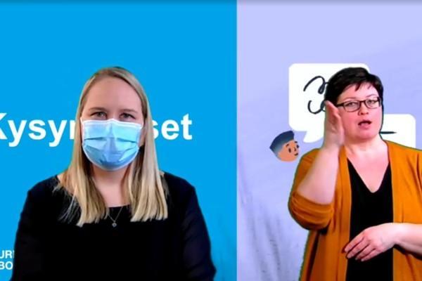 Skärmdump på Jutta Peltoniemi iförd ansiktsmask med teckenspråkstolk i bakgrunden.