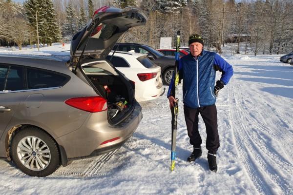 Arto Aunola står vid den öppna bakluckan på sin bil och håller i ett par skidor.
