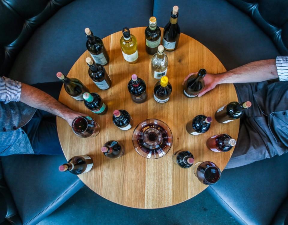 Vinflaskor på ett runt bord, fotade ovanifrån.