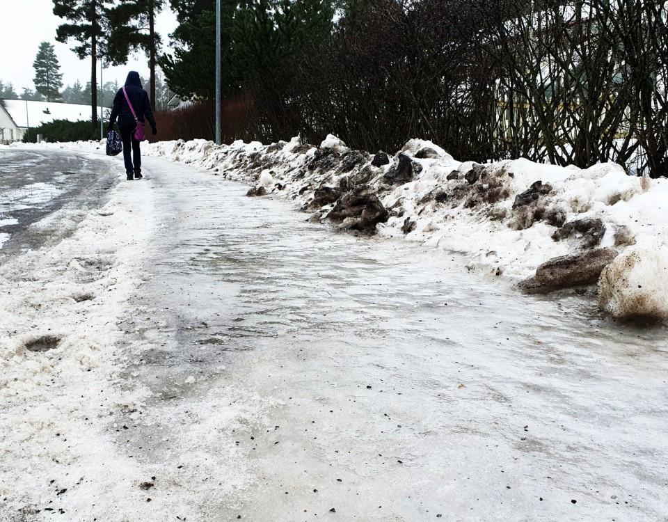 Kvinna som går på isbelagd trottoar.