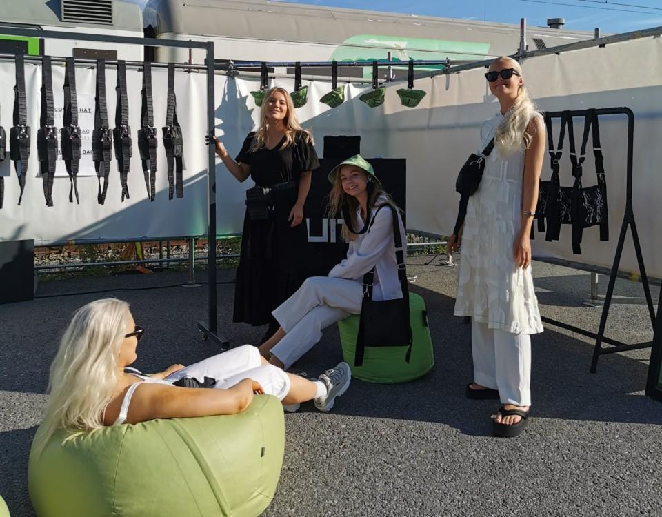Fyra kvinnor på en perrong med olilka accessoarer.